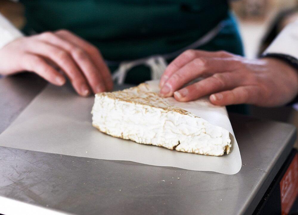 Envolver los quesos en papel encerado es una gran opción para conservar quesos